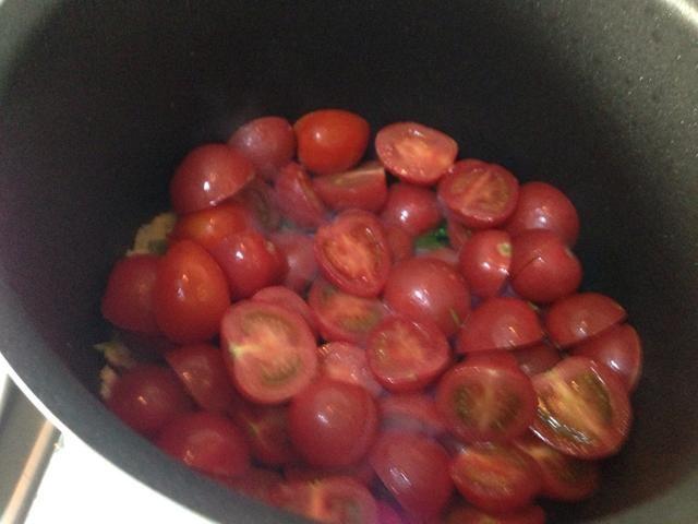 Después de que el ajo se convierten en amarillo, incisa tomates cherry, y siga revolviendo