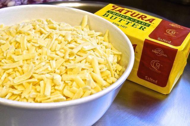 Queso cheddar Triture, también mantequilla para cocinar la salsa.