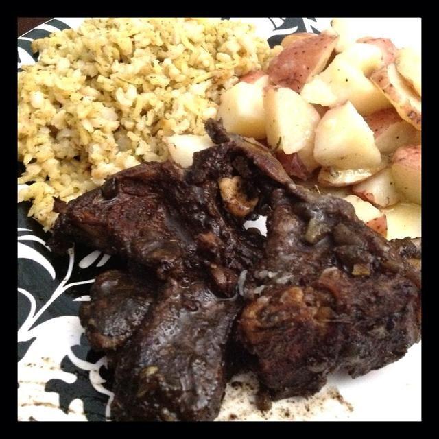 Chuletas de cordero terminadas y servido con patatas al romero y el arroz.