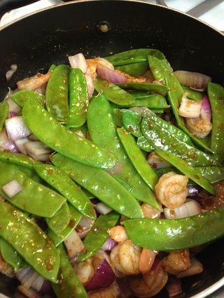 agregue los camarones, los guisantes de nieve y cebolla a la sartén caliente o wok. cocine por tres minutos antes de añadir el castañas de agua, nueces de la India, y la piña.