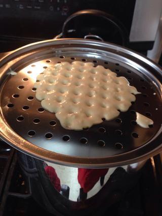 Ponga el rallador en la olla y vierta un poco de pasta en él