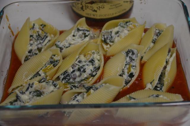 A continuación, tomar conchas de pasta cocida y rellenarlas con la ricotta relleno de espinacas y colocarlas en el plato para hornear.