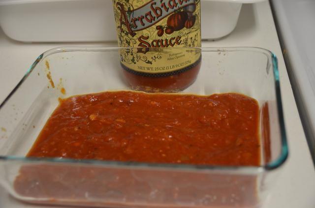 En una fuente de horno difundir un poco de salsa arrabiata. (Cualquier tienda comprado salsa es buena. Trader Joes Aquí he utilizado salsa arrabiata)