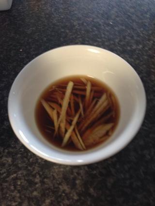 Vierta la salsa de soja suficiente en el plato pequeño para cubrir el jengibre en rodajas y sentarse a un lado.