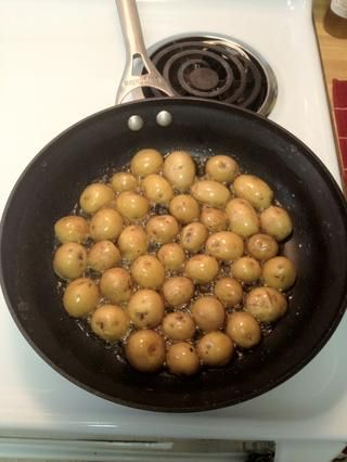 Voltear patatas lado cortado hacia abajo y vierta el aceite de oliva suficiente para patatas capa y el fondo del molde. Encienda el fuego a medio-alto (sobre el número 7) y cocine durante 7-9 minutos, hasta que los fondos de las patatas estén doradas.