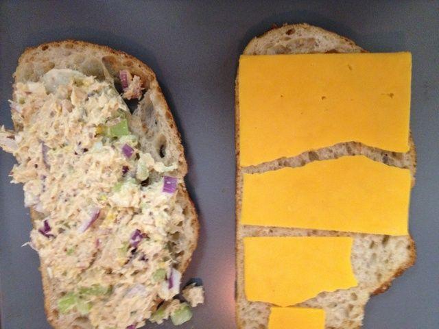 ligeramente la mantequilla ambos lados del pan, añadir el queso y atún. colocar en una bandeja de horno en la parrilla por dos minutos.