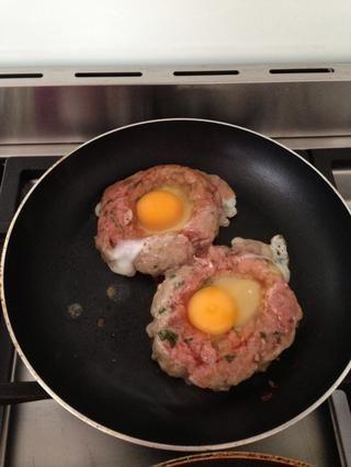 Ponga la hamburguesa en la sartén, y romper un huevo en el centro.