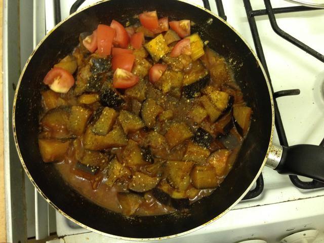 Añadir las especias a la berenjena y mezclar. Picar el tomate en allí también. Deja cocer a fuego lento durante otros 4 minutos, hasta que la berenjena es suave