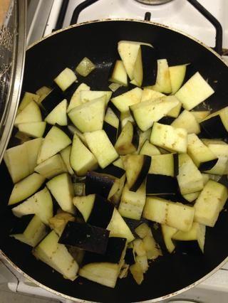 mezcle la cebolla y el ajo con la berenjena picada en una sartén caliente