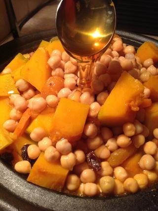 Añadir las frutas, garbanzos secos y tomar una cucharada de miel sobre.