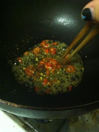 En su wok (fuego medio-alto), añadir su mezcla de salsa y mezclar con los palillos hasta que el azúcar se disuelva. Cuando la salsa comienza burbujeante, añadir sus chiles.