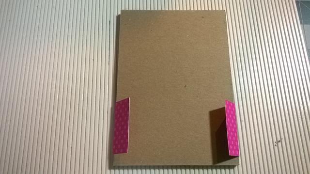 Dobla los bordes del papel en la parte posterior del bloc de notas.