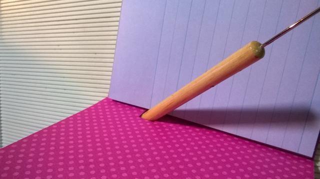 El uso de un extremo romo de su perforador de papel o goma de lápiz empujar suavemente la ranura titular de la pluma.