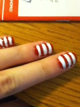 En el rojo, pintar rayas blancas a través de sus uñas. Grueso o fino. ¡Tu elección! Comience con el cepillo en un extremo de la uña y girar el clavo para crear una raya perfecta.