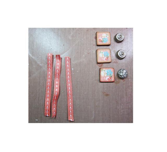 Corte cuatro pequeñas tiras de cinta, cuatro pequeños cuadrados de aglomerado y broches de metal para crear el tiradores. Doble la cinta en el medio / pegamento, luego pegue a la parte posterior del tablero aglomerado y la parte superior con brad.
