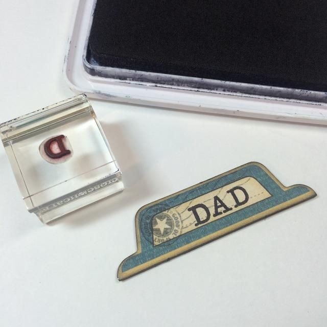 Use un pequeño sello alfabeto para estampar DAD en pieza de aglomerado.