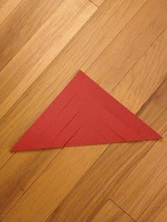 Corte tres incluso cortes en el pliegue inferior del papel. Haga esto en ambos lados del triángulo como se muestra en la imagen.