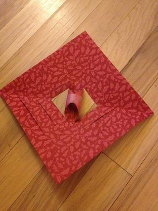 Abre tu pedazo de papel. Enrolle el centro dos cortes en y cinta juntos.