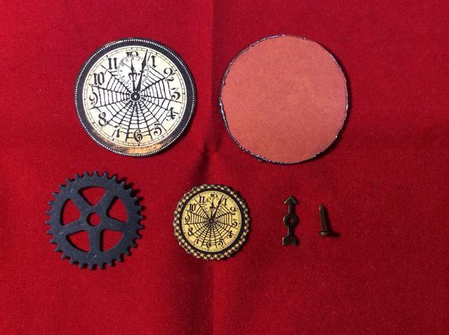 Adherirse gran reloj al centro del círculo naranja. Adherirse pequeño reloj de cremallera negro y el del centro de la gran reloj. Coloque brad y juego de ruleta por el centro.