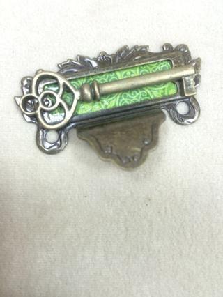 Adherirse un pequeño pedazo de papel verde a la parte de atrás de un tirón la etiqueta de metal, y luego adherir una llave de metal con pegamento fuerte del metal.