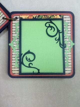 Otras dos piezas de los tapetitos se utilizan aquí. Los troqueles swirly solamente se pegan en los extremos para que pueda insertar una foto a la lona verde.