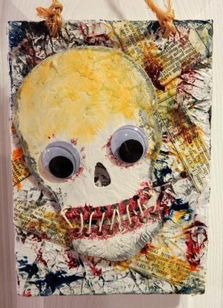 Spritz oro coloraciones en el cráneo, a continuación, añadir la guita a la pieza de la boca juntos. Agregar grandes ojos saltones. Adherirse el cráneo a la lona.
