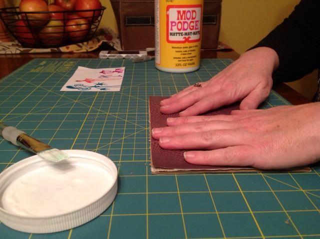 Presione y suavizar el color de fondo en el tablero de cartón / espuma. Recortar los bordes y añadir Mod Podge adicional a lo largo de los bordes si es necesario.