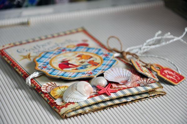 Diseña la portada del mini-álbum con algunas conchas marinas reales, así como algunos de corte difusos de uno de los periódicos. Lazo con un poco de guita.