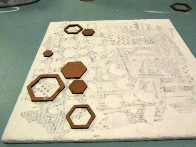 Coloque Um Wow Estudio hexagonal acodada y confeti hexágono piezas de aglomerado de forma aleatoria en la lona en el todavía húmedo Arte Antología estuco.