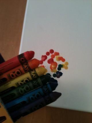 Coloque papel o papel de cera bajo la lona para proteger la superficie de trabajo y poco a poco correr más ligero bajo lápices de colores, mientras que mantiene crayones en caja. Mueva crayones en forma de arco iris o diseño deseado.