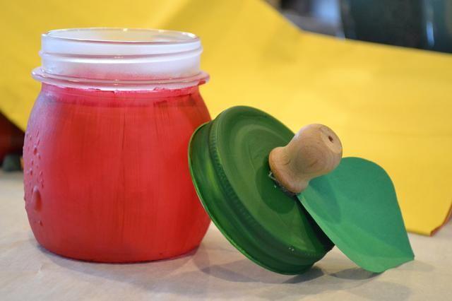 Una vez que ambos se han secado colocar un punto de pegamento en la parte inferior de la perilla de madera. Cortar una forma de la hoja de su papel de construcción verde y colocar la hoja en el pomo. Coloque otro punto de pegamento en la hoja y presione al frasco.