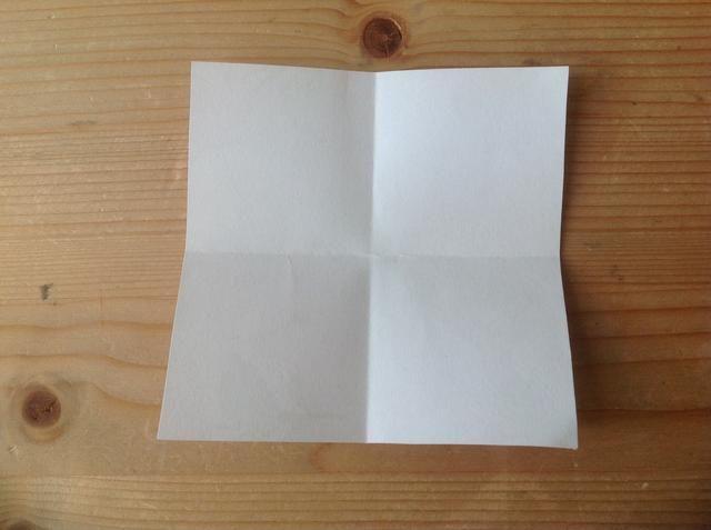 Gire el papel alrededor y doblar en 4 cuadrados pequeños.
