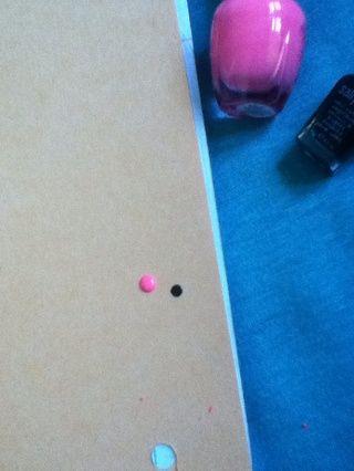 Coloque un punto del melocotón / esmalte de color rosa en el papel.
