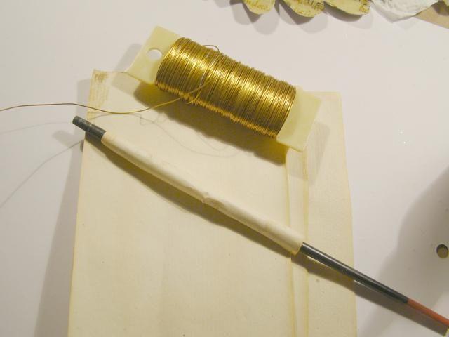 Tome un pequeño pedazo de papel (que tenía un poco de papel viejo libro) enrollarla alrededor del mango de un pincel, lápiz, etc. Corte un pedazo de alambre de metal y se envuelve alrededor de su papel enrollado.