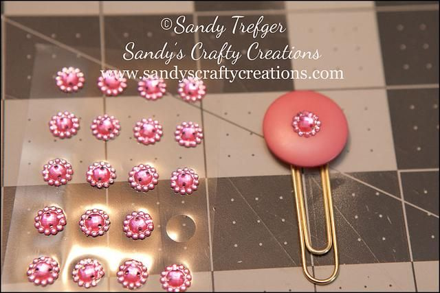 Seleccionar un adorno muy decorativo, como un diamante de imitación o una mariposa o una flor y usar pegamento para unir al centro del botón para ocultar a los ojales.