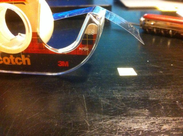 Tome un pequeño pedazo de cinta y doblar sobre un borde (para que sea más fácil tirar hacia arriba). Pon tu pedazo de papel cortado en la cinta y cortar la cinta adicional de descanso. Deje suficiente para que se pegue sin embargo.