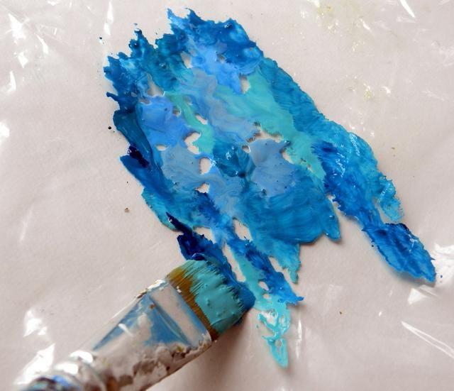 Línea de la mesa con un plástico y aplicar pinturas acrílicas sobre el plástico.