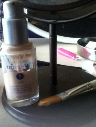Tomando la base de maquillaje favorita y un cepillo de base, la bomba de un chorro de producto sobre el cepillo