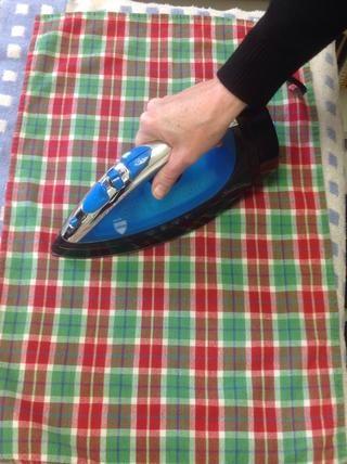 Mueva la plancha alrededor de la toalla.