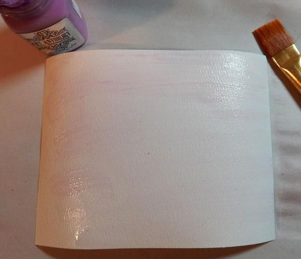Cortar 2 piezas de papel de acuarela para adaptarse frente de la tarjeta, luego rocía con agua y pintar una ligera capa de terciopelo orquídea.
