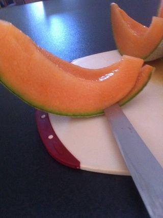 Comenzando en el corte final en la rebanada de melón permanecer cerca de la piel como sea posible. Alrededor de la mitad camino a través de tomar su cuchillo y gire el melón y comenzar de nuevo hasta que te encuentras con tu corte anterior.