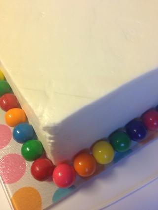 Añade tus bolas de goma alrededor de la base de la tarta. Presione suavemente para adherirse a la crema de vainilla.