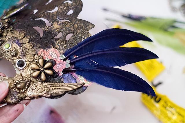 En el otro lado de la máscara puede agregar algunas plumas artificiales, elegí el color azul intenso de las plumas para hacer la máscara aún más brillante. ad algún metal Graphic45 elemento básico en el final y su máscara se hace!