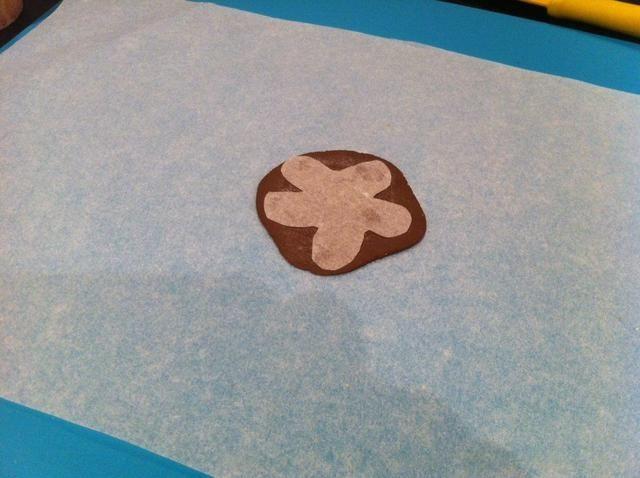 Paso 5. Para la salsa de chocolate, lanzar alguna pasta de azúcar marrón y colocar una plantilla de forma de la flor (a base de papel de hornear) en la parte superior.