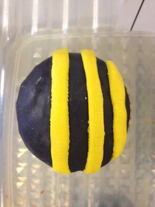 Agregue tres franjas amarillas a cada una de las magdalenas con las tapas negras.