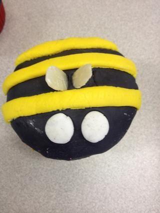 Estirar 10 pequeñas bolas blancas de la formación de hielo y aplanar de dos en cada cupcake para representar los ojos. Pegue dos almendras se deslizaban en cada pastel de abejorros para representar alas.