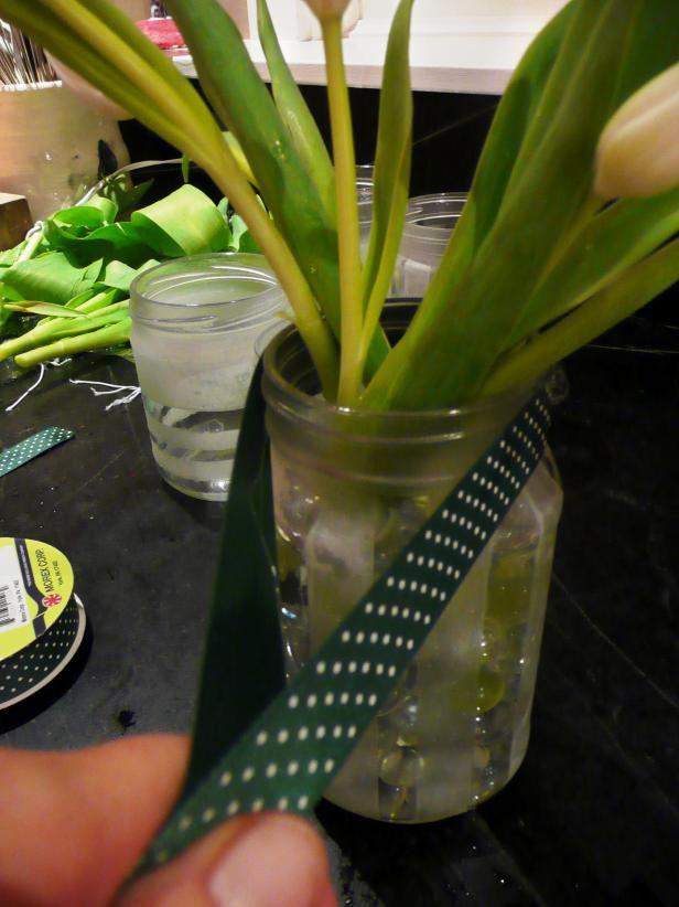 Jarrón frasco de vidrio con la cinta del lunar y flores cortadas