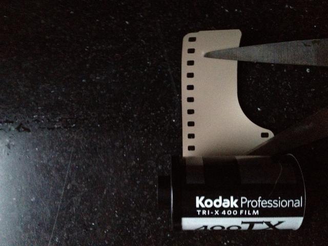 Una vez que estás en la oscuridad, abrir la lata con el abridor de botellas y cortar la ficha de la película para enderezar el borde.