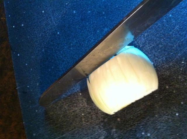 Girar la cebolla y cortar el otro lado, empezando por el lado que se cortó.
