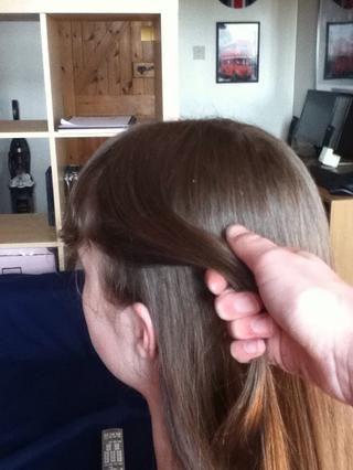 Tome acerca de esta cantidad de pelo por encima de la oreja izquierda.